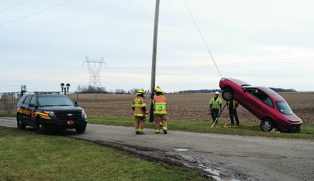 Firefighters from the Fletcher Fire Department, a tow truck driver from Saunder's Towing, and a lineman from Dayton Power & Light, discuss how to safely remove a vehicle that crashed along US Rt. 36, east of Fletcher on Tuesday afternoon, leaving the vehicle stuck on a guy wire that supports a utility pole. The driver, a female whose name has not been released, faces an OVI charge while a male who was involved, Timothy S. Hussong, of New Carlisle, has been charged with obstruction after fleeing on foot. He was captured following a foot chase. The case remains under investigation by the Miami County Sheriff's Department.