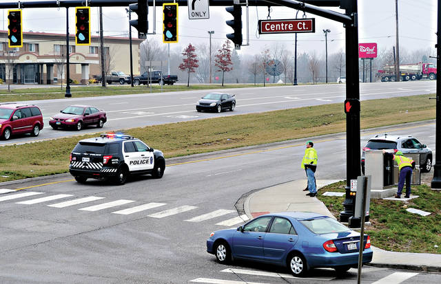 Mike Ullery | Daily Call Officials from the Ohio Department of Transportation monitor traffic signals at East Ash Street and Centre Court as a Piqua police cruiser running lights and siren travels east on East Ash on Tuesday morning. The test was performed with both police and Piqua medic units to test the preemption devices at each intersection. The devices sense oncoming emergency vehicles and control traffic signals accordingly to allow emergency vehicles to safely traverse the intersections.