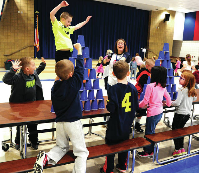 Mike Ullery | Daily Call Grady Stillwell, top, leaps with excitement as his teammates, including Brayden Myers, Chloe Laqui, Layla McDowell, and Aiden Penrod are declared cup-stacking champions by Washington Intermediate School Guidance Councilor Maria Olidiges during Friday's PBIS Good Behavior recognition for third-quarter at the school.