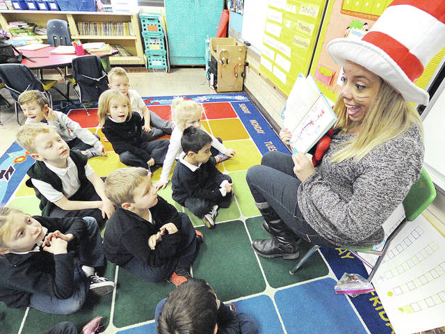 "Anthony Weber | Troy Daily News St. Patrick School kindergarten teacher Rachel Schroerluke reads ""The Cat in the Hat"" with her students Thursday at the school. Schoerluke discussed celebrating Dr. Seuss's 113th birthday and the importance of his work with her students."