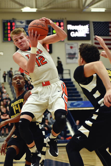 Dale Barger/Civitas Media Versailles' Justin Ahrens grabs a rebound against Roget Bacon Wednesday at Trent Arena.