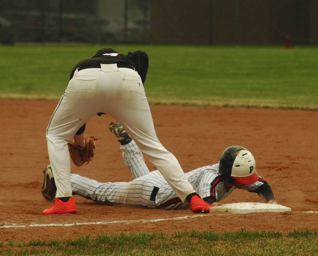 Ron Nunnari/Civitas Media Piqua's Cory Cottrell dives back into first base against Wayne Thursday.