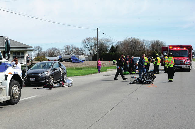 Mike Ullery | Daily Call Medics and firefighters from Covington and Piqua work the scene of a motorcycle vs. car crash at the intersection of US 36 and Mulberry Grove-Rakestraw Road on Sunday morning as CareFlight waits to transport one of the victims from the scene.