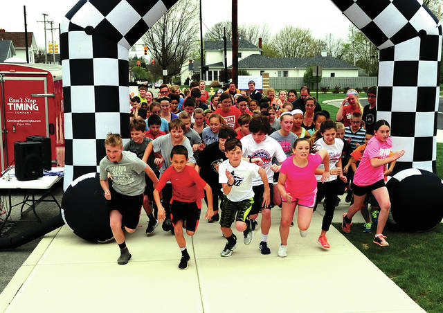 Mike Ullery | Daily Call Fourth, fifth, and sixth grade students from Piqua Central Intermediate School dash from the starting line during a one-mile fun run on Thursday afternoon.