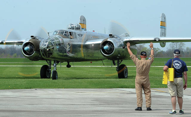 Mike Ullery | Daily Call Plane handlers direct B-25 <em>Miss Mitchell</em> to her place on the ramp at Grimes Airport on Saturday. <em>Miss Mitchell</em> joined more than a dozen other B-25 aircraft in the two-day Grimes B-25 Gathering, which is a prelude to activities at the National Museum of the United States Air Force on Monday and Tuesday honoring the 75th anniversary of General Jimmy Doolittle's Tokyo Raiders bombing of Japan in 1942.