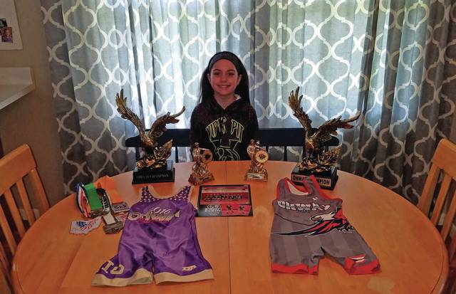 Josh Brown | Troy Daily News Kira Cole, a fourth grader at Cookson Elementary, poses with her wrestling singlets and collection of trophies and medal. Cole is a two-time OH-Way state champion and also wrestles in the Miami Valley Kids Wrestling Association.