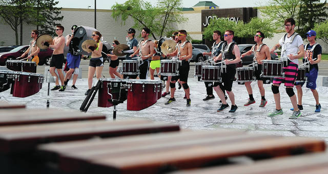 Mike Ullery | Daily Call Members of River City Rhythm Drum & Bugle Corps practice their show in the parking lot of the Miami Valley Centre Mall on Thursday. The group is ouf of Anoka, MN. This is their eighth year staying at the Piqua Comfort Inn while they participate in the annual Drum & Bugle Corps competition at UD Arena.