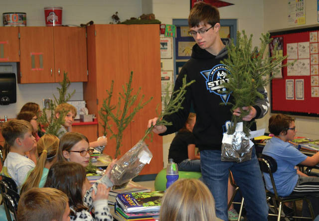 Provided photo FFA chapter officer Alex Isbrandt distributes a tree to a fourth-grade student at Miami East Elementary. All fourth graders received a tree from the FFA as part of a project from the Miami Soil and Water and Troy Foundation.