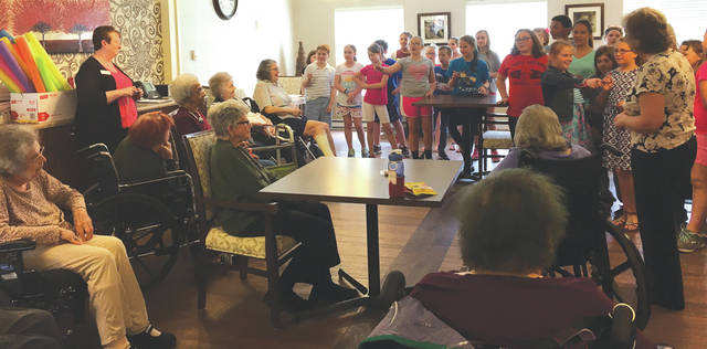 Sam Wildow | Daily Call Kiwanis Kids (K-Kids) learn the names of residents at Piqua Manor after visiting this week to pass out cookies, hang up signs, and connect with residents.