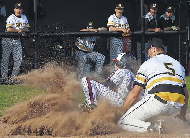 Luke Gronneberg/Civitas Media Piqua's Mick Karn scores a run as Sidney's A.J. Brussell attempts to make a tag Tuesday at Sidney.