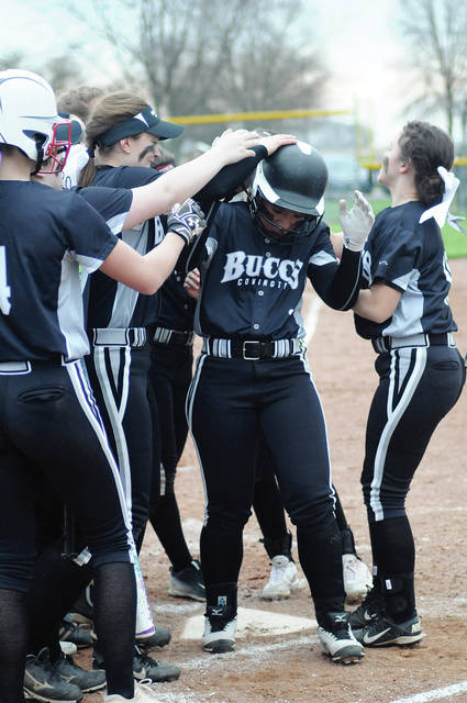 Ben Robinson/GoBuccs.com Justice Warner is congratulated at home plate after hitting a home run against Minster.