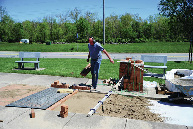 Mike Ullery | Daily Call Brick mason Tim Kearns places bricks around the Veteran's Memorial in Piqua last week as the final batch of bricks is laid in place. Kearns will have the bricks in place in time for the Memorial Day events on May 29.