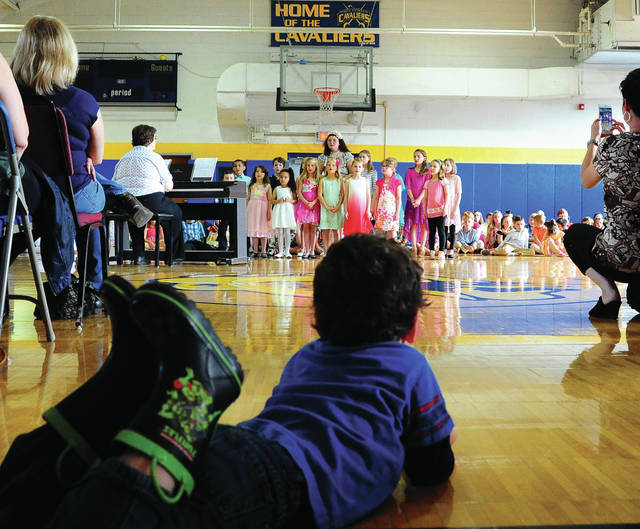 Mike Ullery | Daily Call A young music fan watches the Children's Choir perform <em>Lord, I Lift Your Name On High</em> during the Piqua Catholic Schools Spring Concert at the school on Wednesday evening.