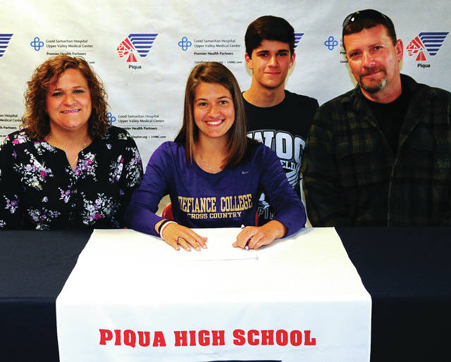 Mike Ullery   Daily Call Piqua High School senior Kenna Bell, center, signs her National Letter of Intent to run track and cross country for Defiance College following her graduation from Piqua. Pictured with Bell are her mom Amanda Haney, brother Kaiden Bell, and stepfather Tony Charles.