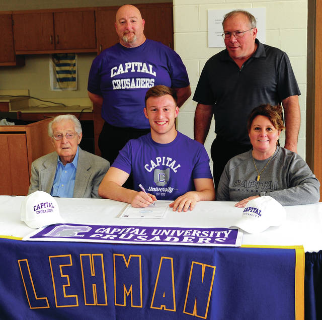 Mike Ullery   Daily Call Lehman Catholic senior Wyatt Long signed his letter of intent to play for Capital University to play football. In front are his grandfather Joe Caserta, Long and his mother Kim Long. In back are his father Bill Long and Lehman Catholic football coach/athletic director Richard Roll.