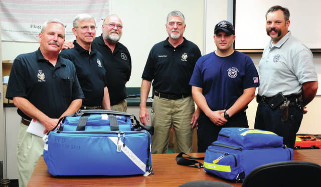 Mike Ullery | Daily Call Troy Elks members Jim Schwartz, John Vetter, Pete Wolf, and Gordon Vance present a check to resupply materials in Pediatric Emergency Care Bags to Piqua Firefighter Brandon Lavy and Assistant Chief Lee Adams at the Piqua Fire House on Tuesday evening.