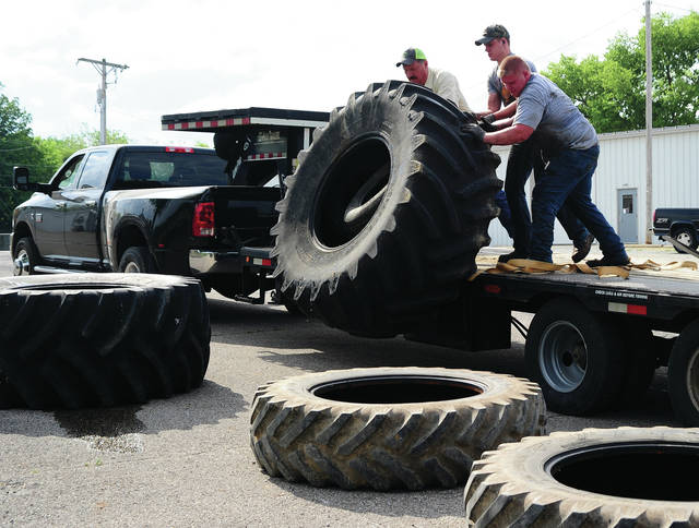 Mike Ullery | Daily Call Miami East FFA members, past and present, unload used tires at the Miami County Fairgrounds on Wednesday as part of the annual tire recycling project for the Miami Soil and Water Conservation District. Linda Ratterman from Miami Soil and Water said that they had approximately 1800 tires brought to the fairgrounds to be recycled.
