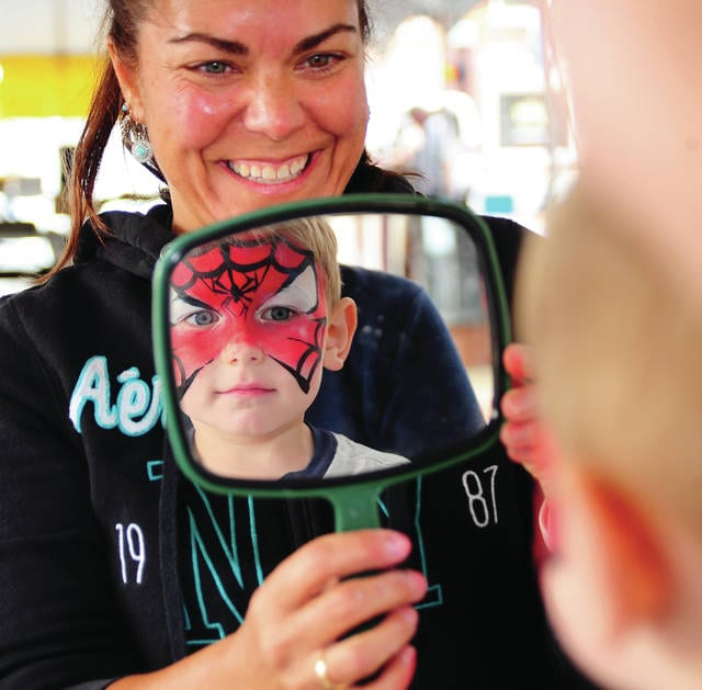 Mike Ullery | Daily Call Spiderman, aka Landon Greene, 3, of Piqua checks out his face paint job as Alter Ego artist Laura Davie holds the mirror during Friday's Taste of the Arts in downtown Piqua.