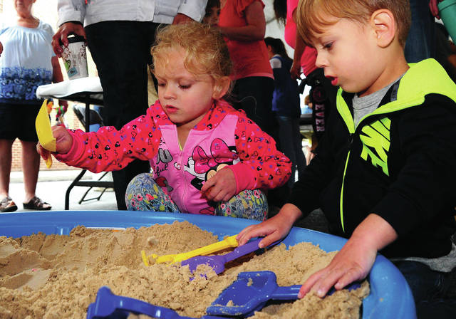 Mike Ullery   Daily Call Aliyah Steinke, 4, and her brother Hunter, 3, explore a sandbox in the Children's Play Area at Taste of the Arts in downtown Piqua on Friday.