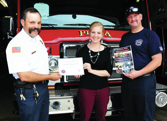 Mike Ullery | Daily Call Lynn Schemmel, Wellness Program instructor at Piqua Central Intermediate School, presents a certificate of appreciation to the Piqua Fire Department on Tuesday. Accepting the certificate for the fire department are Assistant Chief Lee Adams, left, and Firefighter Cleadous Hawk. Also recognized for their assistance in the 2017 Wellness Program were the Piqua Police Department, Piqua Walmart, and Miami County Dental Clinic.