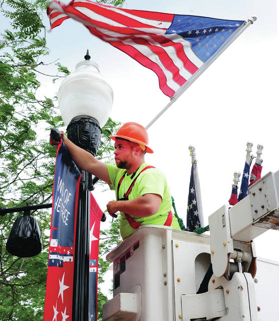 Mike Ullery | Daily Call City of Piqua employee John Cox takes down Taste of the Arts banners in downtown Piqua on Wednesday and replaces them with <em>Land of the Free/Home of the Brave</em> banners, and adds a US Flag as part of preparations to honor our Nation&#8217;s fallen service men and women this coming Memorial Day Weekend.