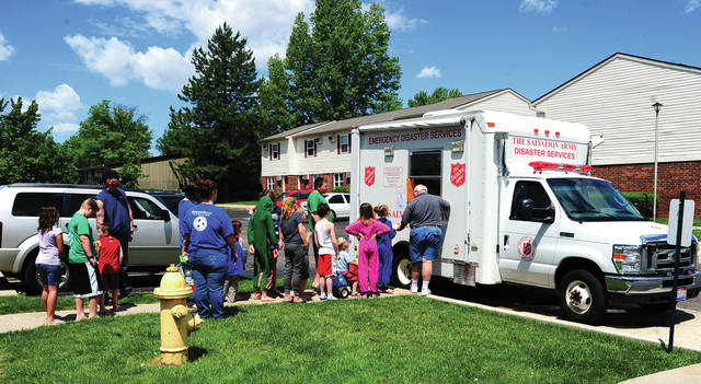 Mike Ullery | Daily Call Youngsters line up at the Salvation Army Food Truck at Piqua Village Apartments on Wednesday as the Summer Feeding Program begins for Piqua children.