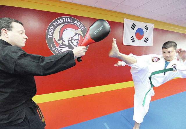 Anthony Weber   Troy Daily News Troy Martial Arts instructor Chris Journell works with Ben Dasal at the studio near the Public Square in downtown Troy.