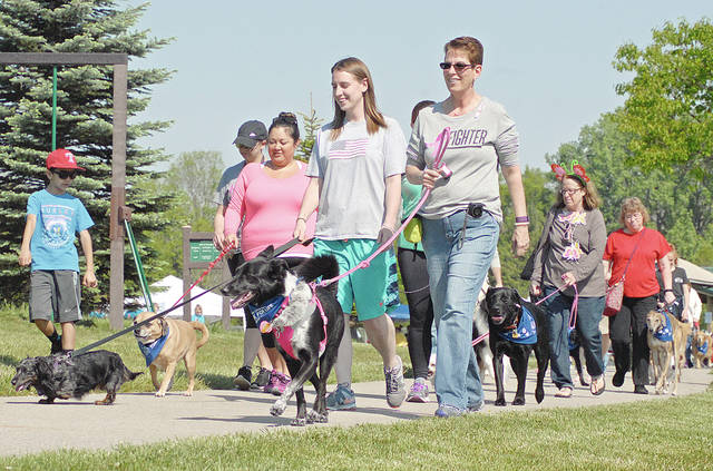 "Anthony Weber | Troy Daily News Cancer survivors, participants and their canine companions walk a mile following the opening ceremony of Bark For Life, a division of Relay For Life, Saturday at Duke Park in Troy. The event offered a blessing of the dogs, raffles, dog games and more than 40 vendors. ""We're here to finish the fight against cancer and pay tribute to our canine friends,"" Jackie Gaier said of the event. According to Gaier it is a way to raise money for the American Cancer Society."