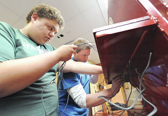 Anthony Weber | Troy Daily News Upper Valley Career Center students, including Sebastian Williams, left, and Jeffrey Wolf, work on a cell phone charging kiosk recently at the school. The unit will be available for use at the Troy Strawberry Festival.