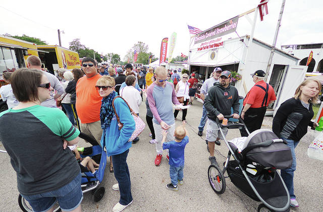 Anthony Weber | Troy Daily News A flood of rally-goers stand in line for chocolate covered strawberries from Troy Post 43 Baseball as well as The Crazy Redhead Canteen recently at the Miami County Food Truck Rally & Competition at the Miami County Fairgrounds in Troy.