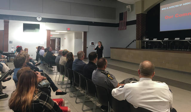 Sam Wildow | Piqua Daily Call Community Outreach Specialist Amy Cost of the Miami County Recovery Council speaks to the approximate 100 attendees at the Heroin and Opioid Education Seminar held in Covington at the Covington K-8 School Monday evening.