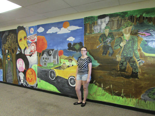 Sam Wildow | Piqua Daily Call Piqua High School junior Heather Lacey poses with her mural of different scenes from American literature in an English classroom.