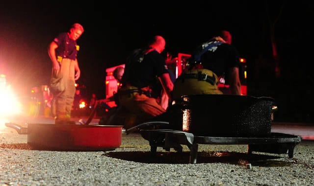 Mike Ullery | Daily Call Firefighters from Troy Fire Department clean up and pack gear following a reported grease fire that started in the pans in the foreground at Park Regency Apartments on West Main Street in Troy on Saturday evening.
