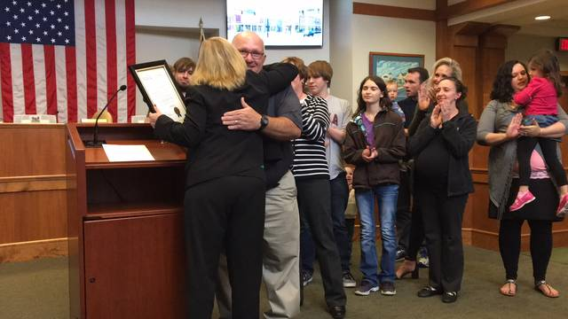 Sam Wildow | Piqua Daily Call Retired Firefighter/Paramedic James William Stein, center, hugs Mayor Kazy Hinds after he and his family accept a resolution of appreciation during the Piqua City Commission meeting Tuesday evening. Stein is retiring after working for the city for 25 years.