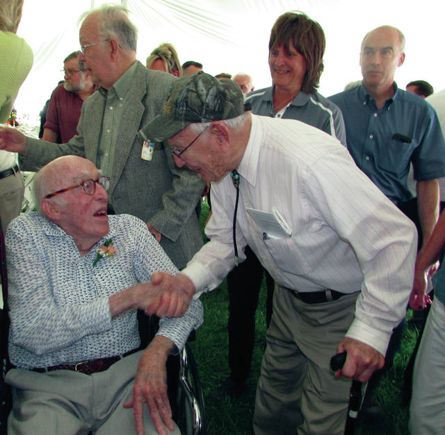 Melanie Yingst | Troy Daily News Former Hobart Brothers Company President William Hobart, 92, left, shakes hands with Carl Phillis Sr., 94, who retired after 47 years in 1987 as the welding division's plant manager at the former Hobart Brothers Manufacturing plant on West Main Street.
