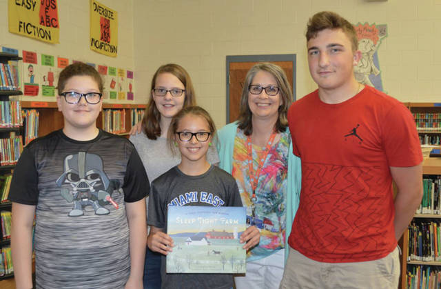 Provided photo Alex DiNardo, right, stands with elementary students, left to right, Aris Ellis, Emily Williams and Addi Jennings (holding the book) with elementary librarian Marisa Digel. The students are all fifth graders.