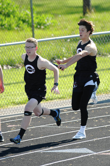 Ben Robinson/GoBuccs.com Covington's Gray Harshbarger hands off to Nathan Lyle in the 800-meter relay Monday.