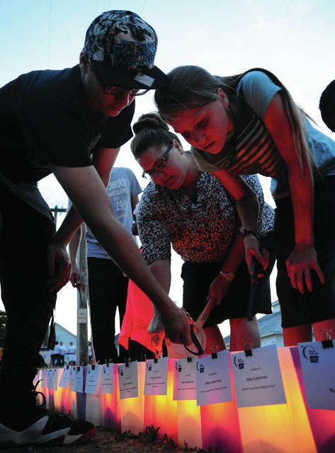 Mike Ullery | Daily Call Rhonda Nelson, along with Jazzlynn, Jacob, and Justice, light candles at Relay For Life on Friday to honor their father Mike Kueterman, who is celebrating 18 years cancer-free, and their mother Becky, who was recently diagnosed with cancer.