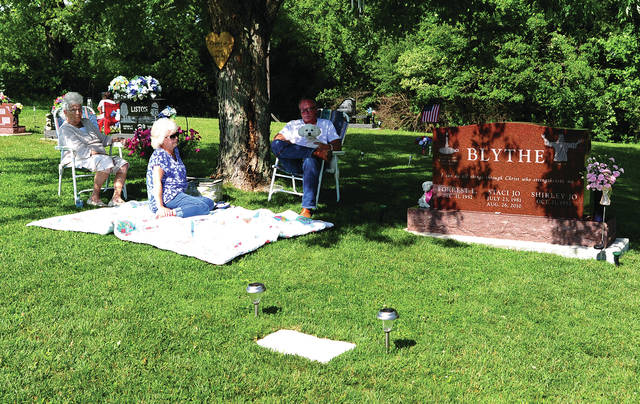 Mike Ullery | Daily Call Forrest and Shirley Blythe of Piqua, right and center, along with Mary Hughes, left, have a Saturday afternoon picnic with their daughter Staci Jo, at Forest Hill Union Cemetery and Arboretum. who is buried there. Staci Jo passed away in 2010. Cemetery officials encourage residents to visit loved ones buried at the cemetery to enjoy the beautiful setting.