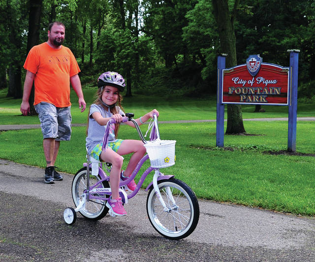 Mike Ullery | Daily Call Bo Lantis and his six-year-old daughter Jacquelynn take a stroll and a ride through Fountain Park on Wednesday evening. The pair are from Piqua.