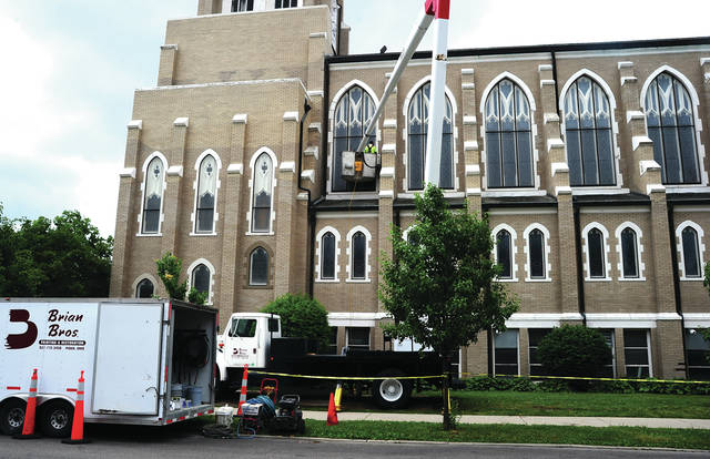 Mike Ullery | Daily Call A painter from Brian Bros. Painting and Restoration uses a bucket truck to reach upper floor trim areas at Greene Street United Methodist Church last week.