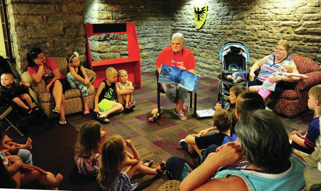 It is summer reading time at the Piqua Public Library as Children's Librarian Sharon Kiser reads a story to a group of children and parents at the library on Thursday. Story time for children is held every Thursday beginning at 10:30 a.m.