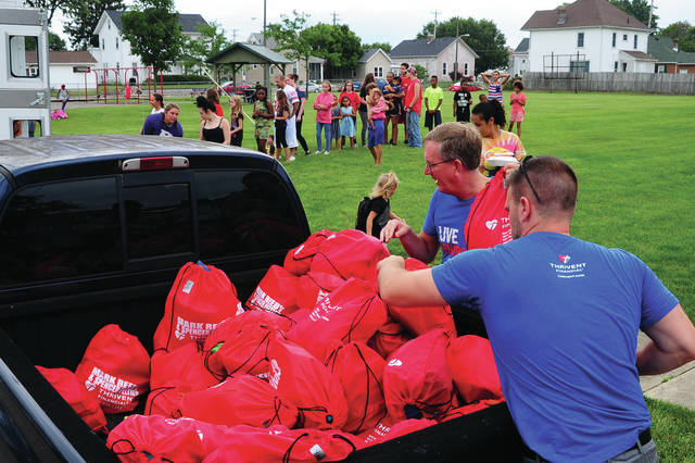 Mike Ullery | Daily Call Mark Reedy and Spencer Peltier, lower right, pass out Summer Survival Kit packs to children at Kiwanis Park during the Salvation Army Food Truck stop on Friday. More than 90 volunteers met at Tecumseh Woods Swimming Pool earlier this week to pack the bags with items such as bubbles, baseballs, towels, and other items for the children to have a fun and safe summer playing outdoors. The bags and contents were donated by Thrivent Financial Group in Piqua.