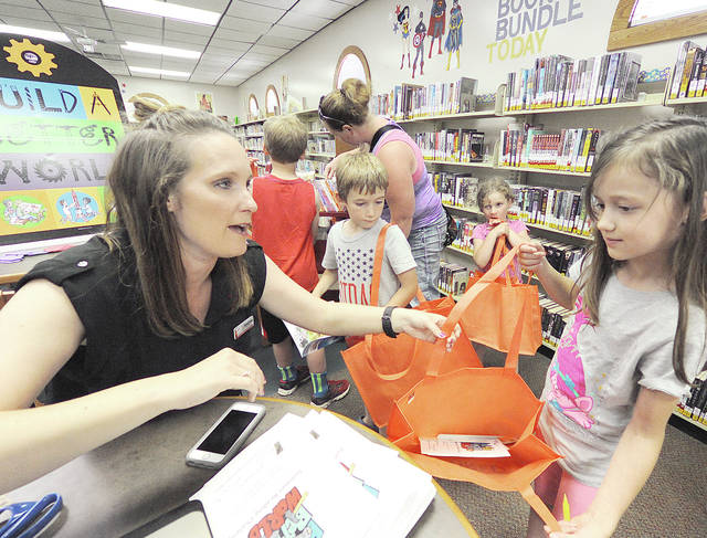 "Anthony Weber | Troy Daily News Oakes-Beitman Memorial Library Branch Supervisor Andrea Wackler helps readers sign-up for the Summer Reading Challenge themed ""Build a Better World."" Here, Stephanie Knepper who was accompanied by her great-grandmother, Jane Ecklebarger (not pictured), registers for the Summer Reading Challenge this week at the library in Pleasant Hill. The Troy-Miami County Public Library, along with the Oakes-Beitman Memorial Library, will assist families with registering for the challenge this week. The program, which promotes independent reading at home, will offer various activities throughout the summer at both locations. Registration will continue into the summer."