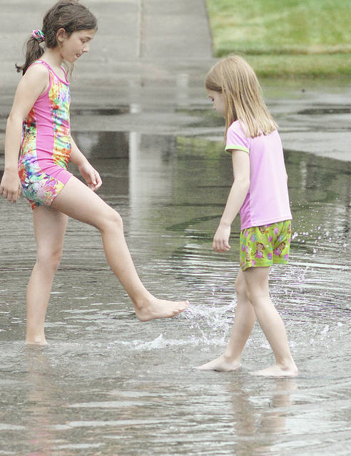 Anthony Weber | Troy Daily News Jean House (not pictured) and her grandchildren Corynne, 10, left, and Eila, 6, splash around through the street in the Sherwood housing development Wednesday as rain fell in the area. According to House, she and her grandchildren wanted to go outside to see if the rain had stopped. She said the rain filled the streets very quickly.