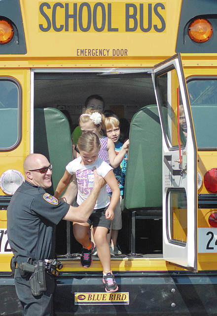 Anthony Weber | Troy Daily News The Troy Police Department is conducting its Safe-T-Town program with children this week at the Troy Junior High School. Officer Nick Freisthler, shown here, assists participants of the program as they exit a school bus. Children had a lesson in crossing through a safe zone as they properly entered a school bus. During the week-long camp, children were given information to help them become more familiar with various subjects regarding safety, including bicycle, electrical, fire and school bus safety. According to Freisthler, on Tuesday, children were taught proper behavior and how to sit safely on a school bus as well as where the exits are located.
