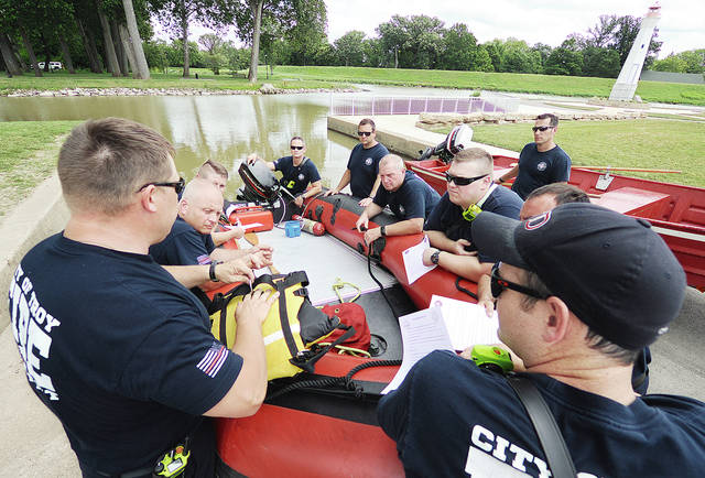 Anthony Weber | Troy Daily News Firefighters from the Troy Fire Department who recently completed a swift water rescue training, including Jason Holfinger, left, and Aaron Simmons, center, were able to apply their knowledge during a training Thursday targeting all shifts of the fire department. Here, firefighters get a refresher course regarding water rescue situations, updated techniques and use of equipment, including a personal floatation device Thursday at Treasure Island Thursday in Troy.