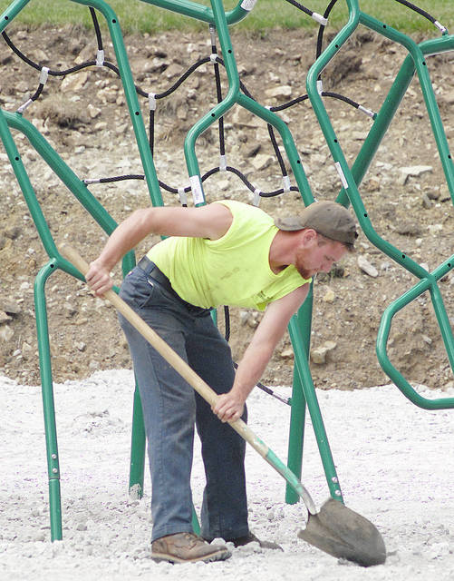 Anthony Weber | Troy Daily News Workers from the West Milton street crew including Joey Smith help to install new playground equipment recently at the park in West Milton. Here, Smith is shown spreading gravel.