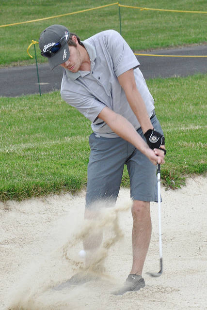 Rob Kiser/Call Photo Trey Hostetter blasts out of the bunker on the 18th hole during the Thursday Industrial League at Echo Hills.