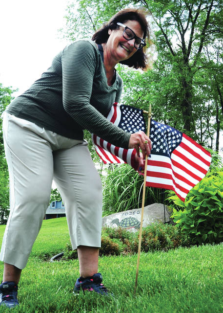 Mike Ullery   Daily Call Becki Reinke, aka the Flag Lady, places US flags along Little Turtle Lane off Hardin Road on Friday. Reinke will place 50 flags along North Woods Hills subdivision and Hardin Road during this Fourth of July weekend and other holidays.